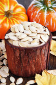 Pumpkin seeds in pot with pumpkins on table close up — Stockfoto