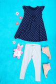 Beautiful clothes for little girl on blue background — Stock Photo
