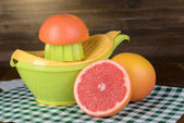 Citrus press and grapefruits on table on wooden background — Stock Photo