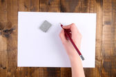 Hand holding pencil and erase with paper on wooden background — Stock Photo