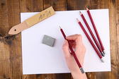 Hand holding pencil with art materials on wooden background — Stock Photo
