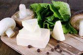 Cream cheese with vegetables and greens on wooden board close-up — Stock Photo