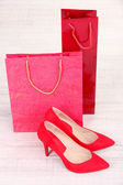 Beautiful red female shoes and shop bags — Stock Photo