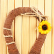Stock Photo: Decorative horseshoe of straw with sunflower, on wooden background