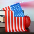 Composition of American flag, books and apple on wooden table, on light background — Stock Photo
