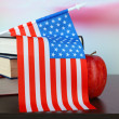 Composition of American flag, books and apple on wooden table, on light background — Stock Photo #38825091