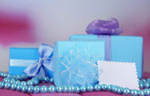 Gift boxes with blank label and chaplet on table on bright background — Stock Photo
