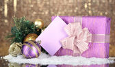 Gift boxes with blank label and Christmas decorations on table on bright background — ストック写真