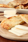 Pita breads with cheese on wooden stands close up — Stock Photo
