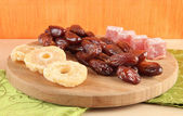 Dried dates with candied pineapples and Turkish delights on table on bamboo background — Stock Photo
