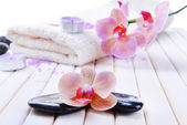 Still life with beautiful blooming orchid flower, towel and spa stones, on color wooden background — Stock Photo