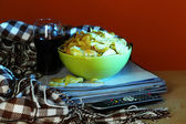 Chips in bowl, cola and TV remote on wooden table on colorful background — Stock fotografie