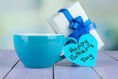 Happy Fathers Day tag with gift box and cup, on wooden table, on light background — Photo
