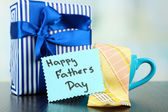 Happy Fathers Day tag with gift boxes, cup and tie, on wooden table, on light background — Foto Stock