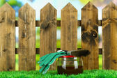 Applying protective varnish to wooden fence, on bright background — Stock fotografie