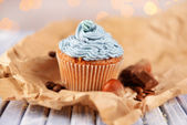 Tasty cupcake with butter cream, on color wooden table, on lights background — Stock Photo
