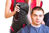 Beautiful girl hairdresser do hairstyle guy in beauty salon — Stockfoto