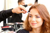 Young guy stylist doing makeup beautiful woman in beauty salon — Stock Photo