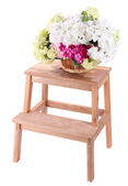 Wicker basket with flowers on small wooden ladder, isolated on white — Stockfoto
