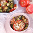 Stuffed tomatoes in pan and bowl on wooden table close-up — Stock Photo