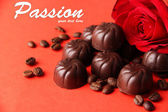 Chocolate candies, on red background — Stockfoto