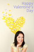 Girl near paper butterflies fly on wall — Stock Photo