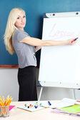 School teacher near whiteboard on blackboard background — Stock Photo
