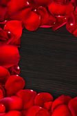 Frame of rose petals on wooden table close-up — Stock Photo