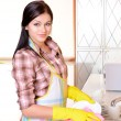 Beautiful young woman washing dishes in kitchen — Stock Photo