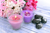 Beautiful colorful candles and flowers,on color wooden background — Stock Photo