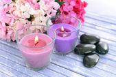 Belles Bougies colorées et fleurs, sur fond de bois de couleur — Photo