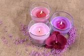 Složení s krásné barevné svíčky, mořská sůl a květy orchidejí, na dřevěné pozadí — Stock fotografie