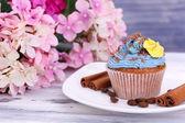 Plaka renk ahşap zemin üzerine tereyağı krema ile lezzetli kek — Stok fotoğraf