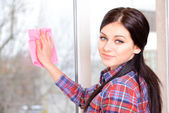Beautiful young woman washing window in room — Stock Photo