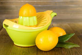 Citrus press and lemons on table on wooden background — Stock Photo