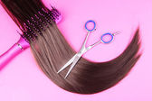 Long brown hair with hairbrush and scissors on pink background — Stock Photo