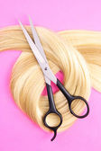 Long blond hair with scissors on pink background — Stock Photo