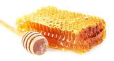 Sweet honeycomb and wooden drizzler, isolated on white — Stock Photo