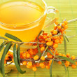 Branches of sea buckthorn with tea on bamboo background — Stock Photo #39040209