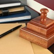 Stock Photo: Wooden stamp with notepads and books on table