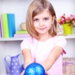 Little girl holding Christmas ball in room — Stock Photo #39042379