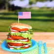 Huge burger on color plastic plate on bright background — Stock Photo #39042837