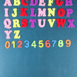 English alphabet and numbers on school desk background — Stock Photo #39045081