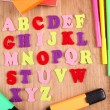 English alphabet, books and markers on wooden background — Stock Photo #39045251