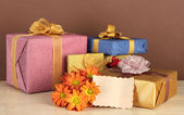 Gift boxes with blank label and flowers on table on brown background — Stock Photo
