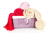 Warm knitted scarves in basket isolated on white — Stock Photo