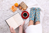 Composition with warm plaid, book, cup of hot drink and female legs, on color carpet background — Stock Photo