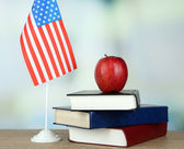 アメリカの国旗、書籍、明るい背景上の木製のテーブルの上のアップルの組成 — ストック写真