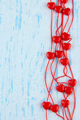 Heart-shaped beads on string on wooden background — Stock Photo