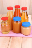 Jars of various baby food, on wooden background — Stock Photo